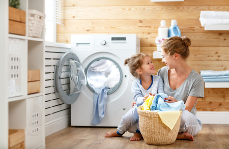 Foto de Happy family mother housewife and child daughter in laundry with washing machine   - Imagen libre de derechos