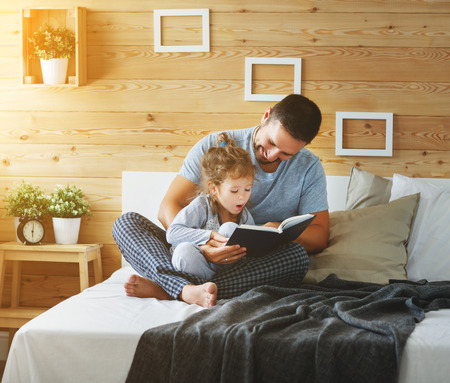 Photo pour happy family father and child daughter reading book in bed  - image libre de droit