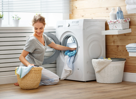 Photo pour a Happy housewife woman in laundry room with washing machine    - image libre de droit