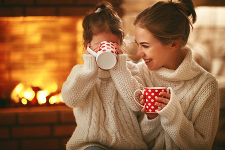Photo pour family mother and child daughter drinking tea and laughing on winter evening by fireplace  - image libre de droit