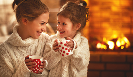 Foto de family mother and child daughter drinking tea and laughing on winter evening by fireplace  - Imagen libre de derechos