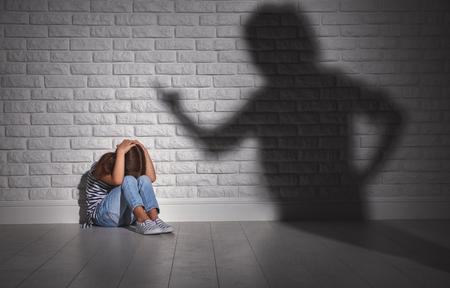Foto de domestic violence. angry mother scolds   frightened daughter sitting on floor  - Imagen libre de derechos