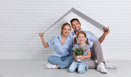 Photo pour concept housing a young family. Mother father and child in new house with a roof at empty brick wall  - image libre de droit