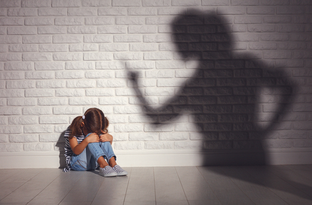 Photo pour domestic violence. angry mother scolds   frightened daughter sitting on floor  - image libre de droit