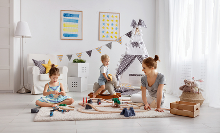 Photo pour family mother and children play a toy railway in the playroom  - image libre de droit