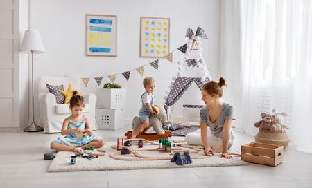 Foto de family mother and children play a toy railway in the playroom  - Imagen libre de derechos