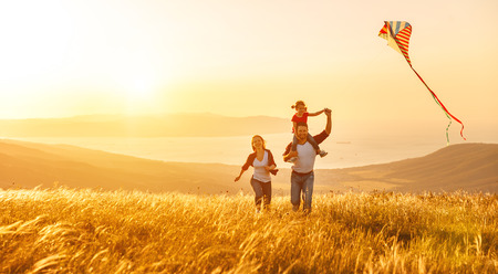 Foto de Happy family father of mother and child daughter launch a kite on nature at sunset - Imagen libre de derechos