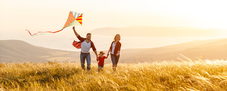 Foto de Happy family father,  mother and child daughter launch a kite on nature at sunset  - Imagen libre de derechos