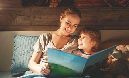 Foto de mother and child daughter reading book in bed before going to sleep   - Imagen libre de derechos