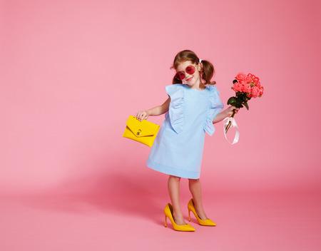 Foto de funny child girl fashionista in big mother's yellow shoes on colored background  - Imagen libre de derechos