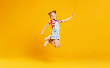 Foto per funny child girl jumping on a colored yellow background  - Immagine Royalty Free