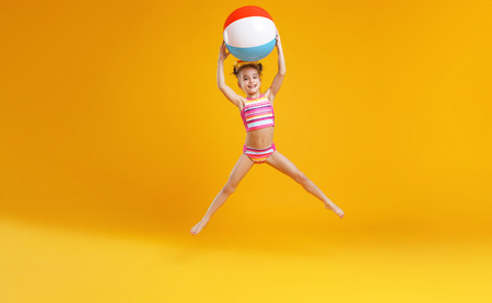 Photo pour  funny happy child   jumping in swimsuit and swimming glasses on colored background  - image libre de droit