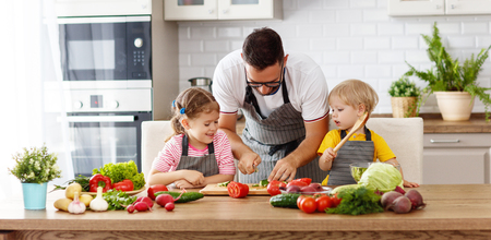 Foto de Father with children preparing vegetable salad at home - Imagen libre de derechos