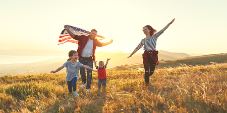 Photo pour happy family with the flag of america USA at sunset outdoors - image libre de droit