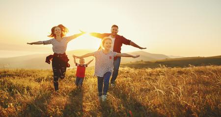 Foto de Happy family: mother, father, children son and  daughter on nature  on sunset - Imagen libre de derechos