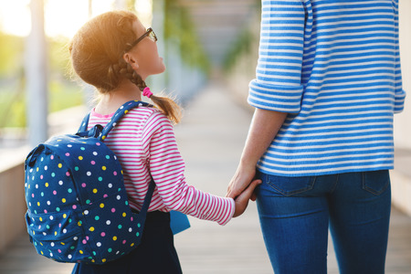 Photo pour first day at school. mother leads a little child school girl in first grade - image libre de droit
