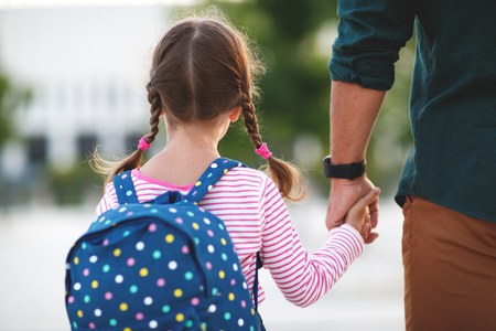 Foto de first day at school. father leads a little child school girl in first grade - Imagen libre de derechos