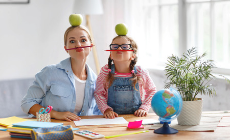 Photo pour funny mother and child daughter doing homework writing and reading at home - image libre de droit