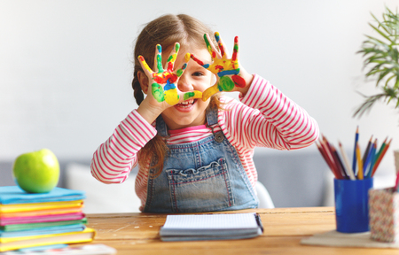 Photo pour happy funny child girl draws laughing shows hands dirty with paint - image libre de droit