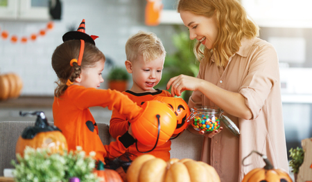 Foto de happy Halloween! a mother treats children with candy at home - Imagen libre de derechos