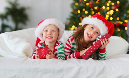 Foto de happy children  in pajamas  with gifts on christmas morning near christmas tree - Imagen libre de derechos