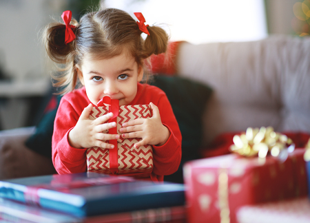 Foto de happy child girl with christmas gifts near christmas tree in morning - Imagen libre de derechos