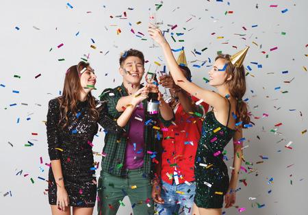 Photo pour corporate party happy friends dancing with confetti and champagne - image libre de droit