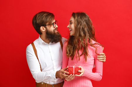 Foto de valentine's day concept. happy young couple with heart, flowers, gift on red background - Imagen libre de derechos