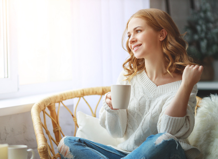 happy young woman drinking morning coffee by the window in winter
