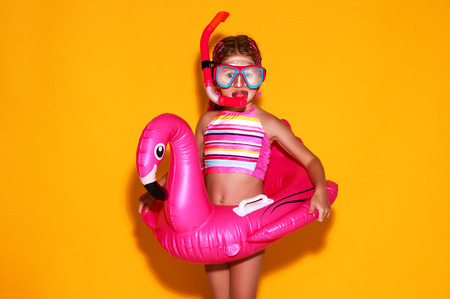 Foto de happy child girl in swimsuit with swimming ring flamingo on a colored yellow background - Imagen libre de derechos