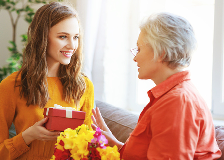 Photo pour Happy mother's day! An adult daughter gives flowers and congratulates an elderly mother on the holiday - image libre de droit
