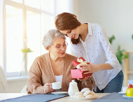 Photo pour Happy mother's day! An adult daughter gives gift and congratulates an elderly mother on the holiday - image libre de droit