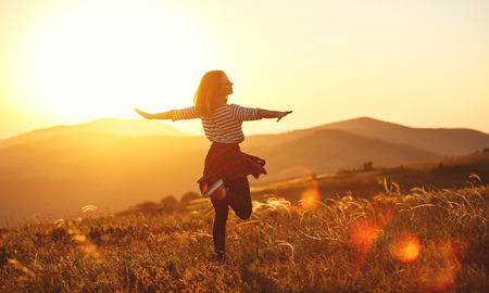 Foto per Happy woman jumping and enjoying life in field at sunset in mountains - Immagine Royalty Free
