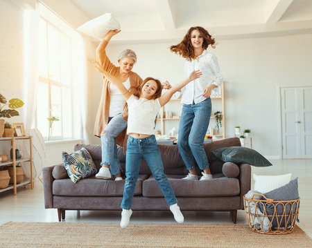 Photo pour Happy family three generations grandmother, mother and child dancing, jumping and laugh at home - image libre de droit