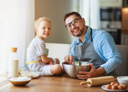 Photo for Happy family in kitchen. Father and child son baking cookies together - Royalty Free Image