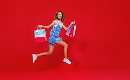 Foto de concept of shopping purchases and sales of happy young girl with packages in red dress on yellow background - Imagen libre de derechos