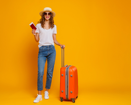 Photo pour concept of travel. happy woman girl with suitcase and passport on  yellow colored background - image libre de droit