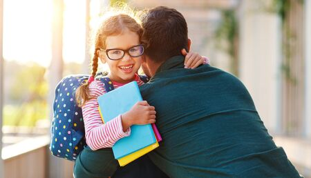 Photo pour first day at school. father leads a little child school girl in first grade - image libre de droit