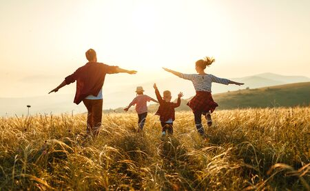 Foto de Happy family: mother, father, children son and  daughter on nature  on sunset - Imagen libre de derechos