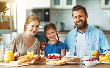Photo pour Happy family mother, father and child daughter have Breakfast in the kitchen in morning - image libre de droit