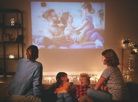 Foto de family mother father and children watching projector, TV, movies with popcorn in the evening   at home - Imagen libre de derechos