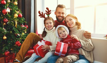 Photo pour happy family with gifts near festive Christmas tree at home - image libre de droit