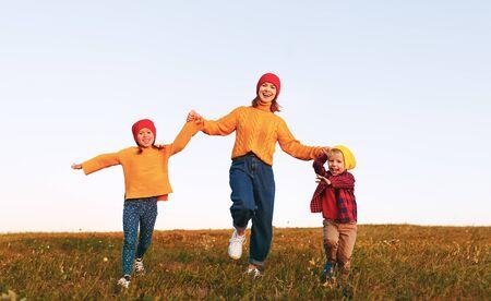Foto de happy family mother and children running in autumn nature at sunset  - Imagen libre de derechos
