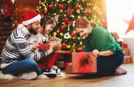 Photo pour happy family mother, father and child with gifts near festive Christmas tree at home - image libre de droit