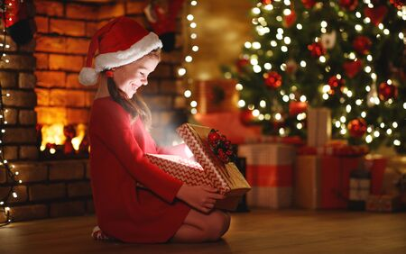 Photo for happy laughing child girl with magic gift sitting  in front of Christmas tree on Christmas Eve - Royalty Free Image