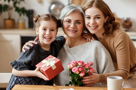 Photo pour mother's day! three generations of a loving family mother, grandmother and daughter congratulate on the holiday, give flowers - image libre de droit