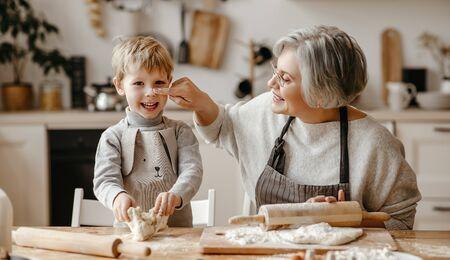 Photo pour Senior woman and little boy   while rolling soft dough during pastry preparation in cozy kitchen at home  - image libre de droit