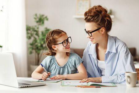 Photo for Pleased mother and small daughter in glasses and casual clothes looking at each other and smiling while sitting at table and school supplies and laptop and doing home task together in light contemporary apartment - Royalty Free Image