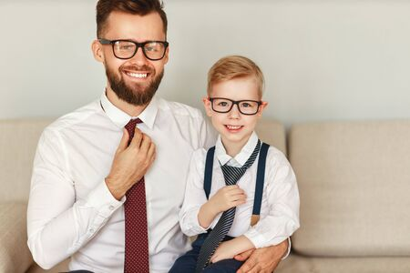 Photo pour A happy bearded businessman in a strict shirt tie and glasses sits with his young son in a similar outfit on the sofa and looks at the camera with a smile - image libre de droit