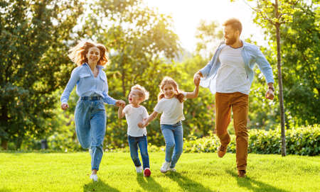 Photo for Excited parents and children smiling and running hand in hand camera on green lawn in summer park - Royalty Free Image